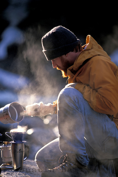 Man making coffee while backpacking.