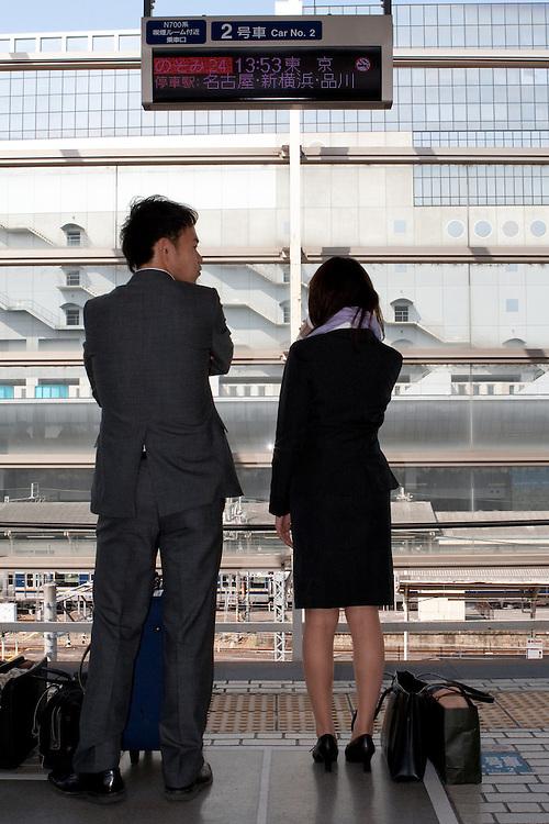 A couple wait for the Shinkasen bullet train in Osaka, Japan