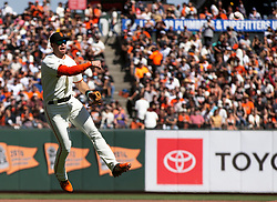 Oct 3, 2021; San Francisco, California, USA; San Francisco Giants third baseman Evan Longoria (10) leaves his feet to throw out San Diego Padres shortstop Fernando Tatis Jr. at first base during the fourth inning at Oracle Park. Mandatory Credit: D. Ross Cameron-USA TODAY Sports