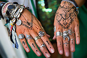 Glastonbury Festival, 2015.<br /> Girl with mehndi [henna tattoos] on her hands with silver rings, bracelets and wristbands. Henna tatoos on top of the hand symbolises protection.