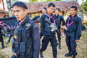 31 OCTOBER 2012 - YARANG, PATTANI, THAILAND: Thai soldiers prepare to escort villagers from Wat Kohwai on a procession to Yala for Ok Phansa. Ok Phansa marks the end of the Buddhist 'Lent' and falls on the full moon of the eleventh lunar month (October). It's a day of joyful celebration and merit-making. For the members of Wat Kohwai, in Yarang District of Pattani, it was a even more special because it was the first time in eight years they've been able to celebrate Ok Phansa. The Buddhist community is surrounded by Muslim villages and it's been too dangerous to hold the boisterous celebration because of the Muslim insurgency that is very active in this area. This the year the Thai army sent a special group of soldiers to secure the village and accompany the villagers on their procession to Yala, a city  about 20 miles away.   PHOTO BY JACK KURTZ