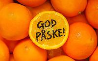 Påskehilsenen «God påske!» skrevet på en skåret appelsin liggende på en seng av appelsiner.