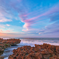 South Florida sunset photography from Coral Cove Park in Tequesta, FL of Palm Beach County, a perfect winter escape destination. That night, the waves of the Atlantic Ocean and the reef were beautifully illuminated by the sunset light painting them in warm hues. <br />