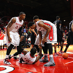 Junior Etou #10 of the Rutgers Scarlet Knights is helped up by teammates after scoring a basket and drawing the additional foul during the second half of Rutgers men's basketball vs Temple Owls in American Athletic Conference play on Jan. 1, 2014 at Rutgers Louis Brown Athletic Center in Piscataway, New Jersey.