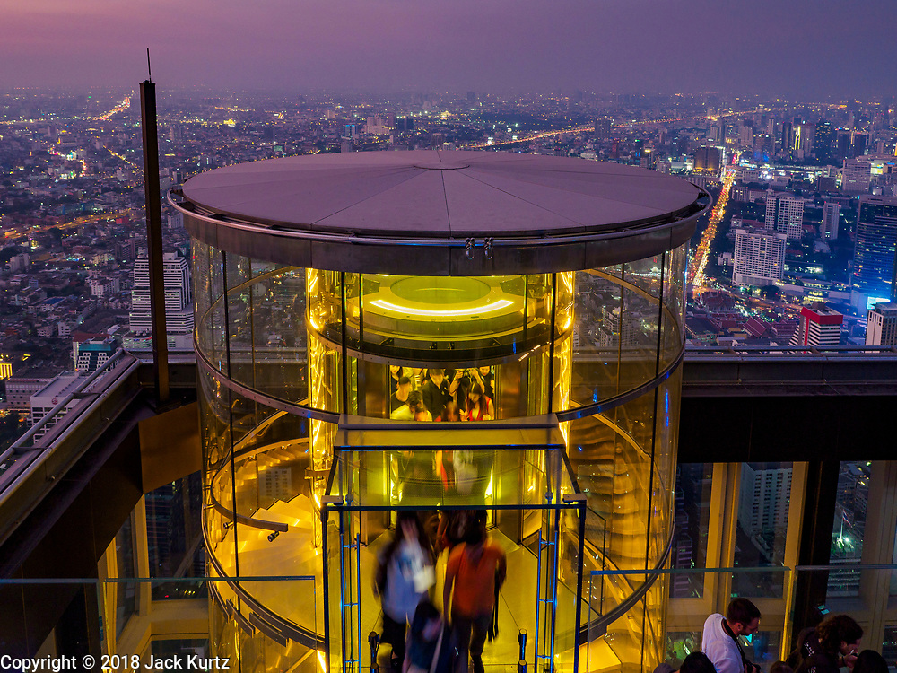 27 DECEMBER 2018 - BANGKOK, THAILAND: Sightseers get off the elevator that brings people to rooftop observation deck of the King Power Maha Nakhon Tower. The MahaNakhon Skywalk, at the top of the King Power Maha Nakhon Tower, is 1,030 feet (314 meters) above street level. It is the tallest building and highest vantage point in Bangkok. The skywalk opened in November and has been drawing large crowds.    PHOTO BY JACK KURTZ
