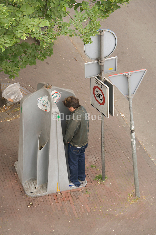 man urinating in an open outdoor urinal Amsterdam Holland