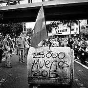 Caracas - Venezuela. In the middle of a protest, manifestants roll a concrete pipe with the numbers of 25.000 murders in Venezuela for 2013. Even if this number is calculed on the highest line, no offical data is known since 2005 when government stopped giving official numbers about violence.