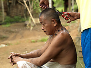 A Tai Dam man has a haircut in Ban Na Mor village, Oudomxay province, Lao PDR