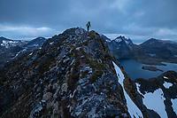 Female hiker on narrow summit ridge of Narvtind mountain peak, Moskenesøy, Lofoten Islands, Norway