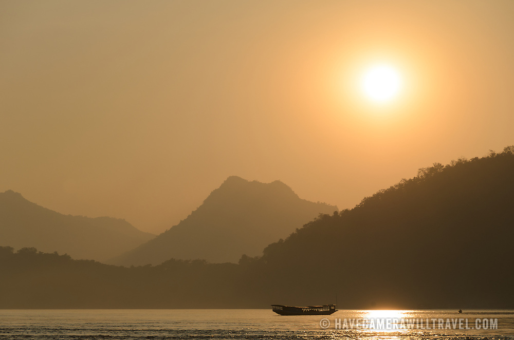 Layers of hills are silhouetted against the sunset on the Mekong River near Luang Prabang, Laos.