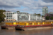 Waste barges on the river Thames opposite new apartment buildings.