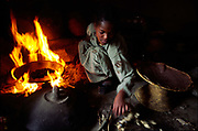 A Ethiopian child in the Northern Highlands cooking njera (staple bread) in her home, Ethiopia.