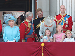 (left to right) Queen Elizabeth II, Duchess of Sussex, Prince of Wales looking at the Duke of Sussex, Duchess of Cambridge holding Princess Charlotte, Duke of Cambridge holding Prince George and Savannah Phillips on the balcony of Buckingham Palace, in central London, following the Trooping the Colour ceremony at Horse Guards Parade as the Queen celebrates her official birthday.
