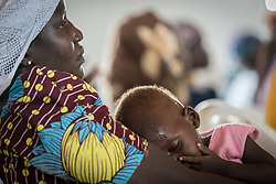31 May 2019, Mokolo, Cameroon: A young girl sleeps in her mother's lap, as they wait their turn, at a distribution of non-food items in Minawao. The Minawao camp for Nigerian refugees, located in the Far North region of Cameroon, hosts some 58,000 refugees from North East Nigeria. The refugees are supported by the Lutheran World Federation, together with a range of partners.
