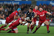 Kieron Fonotia of the Ospreys ©, despite being surrounded by Scarlets players gets his pass away to teammate Jeff Hassler (not in pic)  Guinness Pro14 rugby match, Ospreys v Scarlets at the Liberty Stadium in Swansea, South Wales on Saturday October 7th 2017. <br /> pic by Andrew Orchard, Andrew Orchard sports photography.