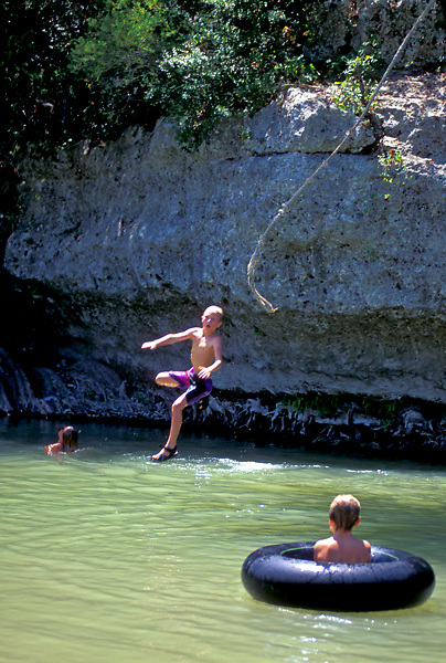 Stock photo of a boy jumping into the river as a friend in inner tube watches