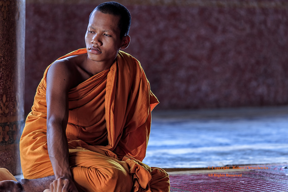 A young Buddhist monk sits in a reflective way sitting in the marble main temple to avoid the midday heat, Wat Bovil, Battamgbang Cambodia.