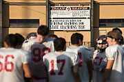 A sign marking the accomplishments of the Iraan High School football team hangs in the distance while the football team practices in Iraan, Texas on December 13, 2016. (Cooper Neill for The New York Times)