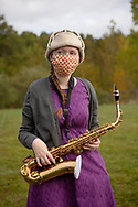 CLIENT: THE HEWLETT FOUNDATION / ALLIANCE FOR EXCELLENT EDUCATION<br /> <br /> Student with saxophone, Middletown High School in Middletown, CT, October, 2020. To limit the spread of Covid-19, band practice is taking place on the football field and all wind instruments have been provided with sock-like horn covers.