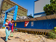 "15 FEBRUARY 2019 - SIHANOUKVILLE, CAMBODIA: A Cambodian woman carries her child past a the construction site of a Chinese casino in Sihanoukville. There are about 80 Chinese casinos and resort hotels open in Sihanoukville and dozens more under construction. The casinos are changing the city, once a sleepy port on Southeast Asia's ""backpacker trail"" into a booming city. The change is coming with a cost though. Many Cambodian residents of Sihanoukville  have lost their homes to make way for the casinos and the jobs are going to Chinese workers, brought in to build casinos and work in the casinos.    PHOTO BY JACK KURTZ"