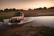 Safari vehicle carrying tourists crossing water at sunset, South Luangwa National Park, Zambia