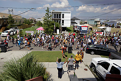 29 August 2015. Lower 9th Ward, New Orleans, Louisiana.<br /> Hurricane Katrina 10th anniversary memorials.<br /> A second line passes down Tennessee Street in front of Brad Pitt inspired make it Right homes. <br /> Photo credit©; Charlie Varley/varleypix.com.