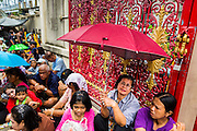 "09 AUGUST 2014 - BANGKOK, THAILAND:      People sit under umbrellas while they wait for a food distribution to start at the Ruby Goddess Shrine in the Dusit section of Bangkok. The seventh month of the Chinese Lunar calendar is called ""Ghost Month"" during which ghosts and spirits, including those of the deceased ancestors, come out from the lower realm. It is common for Chinese people to make merit during the month by burning ""hell money"" and presenting food to the ghosts. At Chinese temples in Thailand, it is also customary to give food to the poorer people in the community.    PHOTO BY JACK KURTZ"
