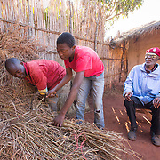 CAPTION: As his family members observed how ACAMO was changing his life, they resolved to redouble their efforts to support him wherever possible. His sons help him with tasks he can't easily complete himself, such as replacing the thatch on the roof of their home. Nevertheless, Caisse is determined to be independent wherever possible. A collapsible white cane provided to ACAMO members with CU's support has helped him in moving around within the family compound without anyone's assistance. He has even trained himself to use this to guide him while carrying a bucket of water for bathing. LOCATION: Nzinje Village, Lichinga, Niassa Province, Mozambique. INDIVIDUAL(S) PHOTOGRAPHED: From left to right: Domingos Casimiro, Lázaro Casimiro and Casimiro Adua Caisse.