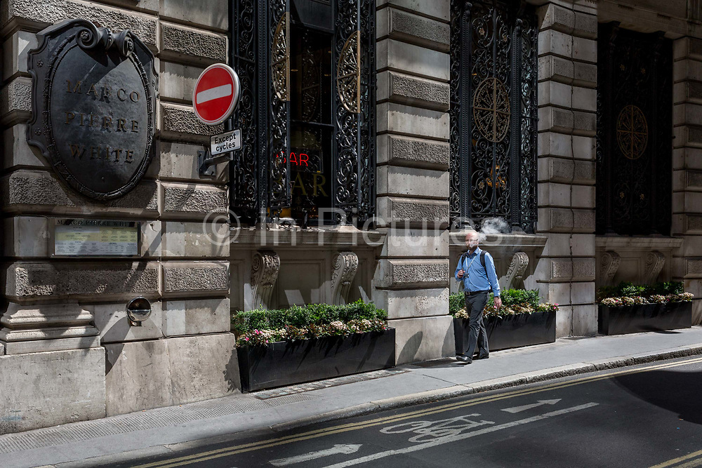 A male vaper smokes while walking along Finch Street, a narrow medieval-era lane in the City of London, the capitals historic financial district, on 2nd August 2018, in London, England.