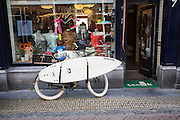 In Utrecht staat voor een winkel met onder andere surfbenodigheden en -kleding een fiets met een surfplank.<br /> <br /> A bike with a surfing board is parked in front of a surfing shop in Utrecht.