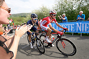 Cheered and applauded by fans behind barriers, Mark Christian (Aqua Blue Sport) and Anthony Perez (Cofidis, Solutions Credits) chase the leader of the race on the Côte de la Redoute climb during the 2018 Liège-Bastogne-Liège elite men's race on Sunday 22 April 2018.