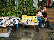 15 OCTOBER 2016 - BANGKOK, THAILAND:  A vendor, with his daughter on his knee, sells portraits of Bhumibol Adulyadej, the King of Thailand, near the Grand Palace in Bangkok. King Bhumibol Adulyadej died Oct. 13, 2016. He was 88. His death comes after a period of failing health. With the king's death, the world's longest-reigning monarch is Queen Elizabeth II, who ascended to the British throne in 1952. Bhumibol Adulyadej, was born in Cambridge, MA, on 5 December 1927. He was the ninth monarch of Thailand from the Chakri Dynasty and is known as Rama IX. He became King on June 9, 1946 and served as King of Thailand for 70 years, 126 days. He was, at the time of his death, the world's longest-serving head of state and the longest-reigning monarch in Thai history.     PHOTO BY JACK KURTZ