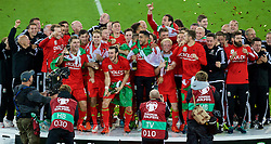 CARDIFF, WALES - Tuesday, October 13, 2015: Wales players celebrate after qualifying for the finals following a 2-0 victory over Andorra during the UEFA Euro 2016 qualifying Group B match at the Cardiff City Stadium. goalkeeper Owain Fon Williams, masseur Chris Senior, physiotherapist Sean Connelly, sport psychologist Ian Mitchall, Medical Officer Doctor Jon Houghton, Sam Vokes, Ben Davies, David Edwards, Sam Vokes, James Chester, Gareth Bale, captain Ashley Williams, Neil Taylor, Jonathan Williams, manager Chris Coleman, Andy King, Aaron Ramsey, masseur David Rowe, James Turner, Chris Gunter, Joe Ledley, physiotherapist David Weeks, Kevin McCusker. (Pic by Paul Currie/Propaganda)