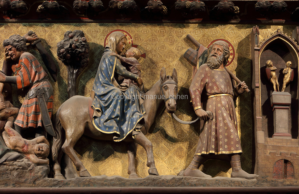 Flight into Egypt, painted carved section of the North choir screen, between the ambulatory and the sanctuary, carved 1300-50, by Pierre de Chelle, Jean Ravy and Jean Le Bouteiller, in the Cathedrale Notre-Dame de Paris, or Notre-Dame cathedral, built 1163-1345 in French Gothic style, on the Ile de la Cite in the 4th arrondissement of Paris, France. Mary rides on a donkey carrying the infant Jesus, sharing a tender loving moment with him, while Joseph walks ahead, glancing behind to check whether they are followed. On the left is the Massacre of the Innocents and on the right, idols fall away. Picture by Manuel Cohen