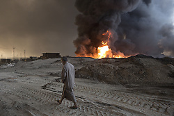 October 21, 2016 - Qayyarah, Iraqi-Kurdistan, Iraq - An Iraqi man walks past a burning oil well, one of several located on the edge of the neighbourhood where he lives in Qayyarah, Iraq. The wells, part of a large oilfield around the town, were set alight by retreating Islamic State militants in July 2016, but have yet to be extinguished. ..Since being retaken from the Islamic State the town of Qayyarah has become an important staging post for the Iraqi Army, and some US support elements, in the buildup to the Mosul offensive. (Credit Image: © Matt Cetti-Roberts/London News Pictures via ZUMA Wire)