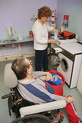 Carer doing washing in kitchen with man with Cerebral Palsy; who is wheelchair user,