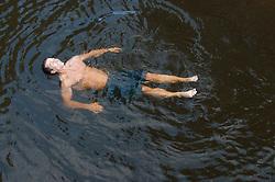 man enjoying floating in a river