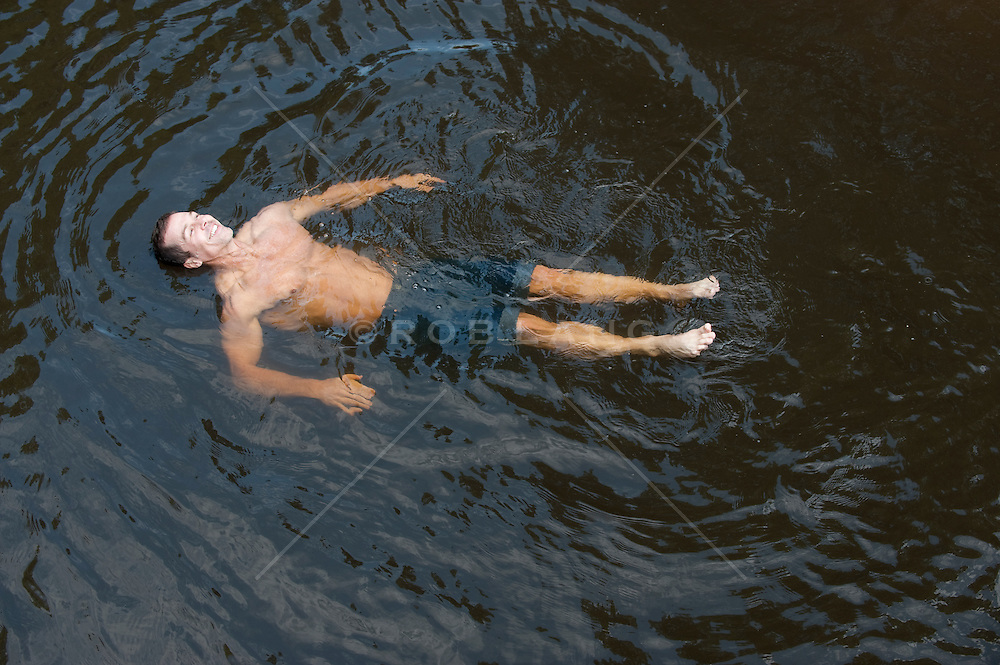 man enjoying floating in a river