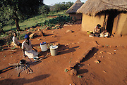 "The Northern Province of South Africa, formerly the Northern Transvaal and now called the Mpumalanga, is home to the Vendan people. Here, Muditami Munzhedzi, in traditional Venda clothing, prepares the Vendan's daily staple of cornmeal porridge as well as mopane worms. Tshamulavhu, Mpumalanga, South Africa. ""Mopane"" refers to the mopane tree, which the caterpillar eats. Dried mopane worms have three times the protein content of beef and can be stored for many months. Image from the book project Man Eating Bugs: The Art and Science of Eating Insects."