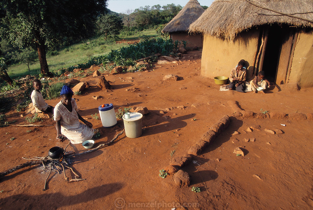 """The Northern Province of South Africa, formerly the Northern Transvaal and now called the Mpumalanga, is home to the Vendan people. Here, Muditami Munzhedzi, in traditional Venda clothing, prepares the Vendan's daily staple of cornmeal porridge as well as mopane worms. Tshamulavhu, Mpumalanga, South Africa. """"Mopane"""" refers to the mopane tree, which the caterpillar eats. Dried mopane worms have three times the protein content of beef and can be stored for many months. Image from the book project Man Eating Bugs: The Art and Science of Eating Insects."""