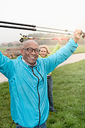 Senior couple stretching before Nordic walk with hiking poles, Bavaria, Germany