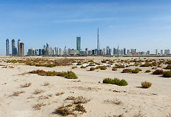 Skyline of Dubai with Burj Khalifa tower prominent and desert in foreground in United Arab Emirates , UAE