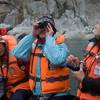 Tourists in a Zodiac raft explore Seno Chico (Small Fjord) in Alberto de Agostini National Park, Tierra del Fuego, Chile.