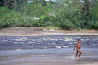 Niño indígena desnudo caminando en el río Autana , Amazonas, Venezuela.