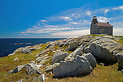 Rocky shoreline along the Atlantic Coast with old granite lighthouse<br /> Rose Blanche<br /> Newfoundland <br /> Canada