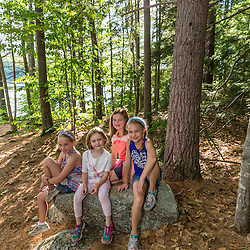 Four girls on a rock near Page Pond in Meredith, New Hampshire.