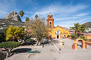 The Parroquia San Sebastian church with the massive monolith rock called the Pena de Bernal in the beautiful colonial village of Bernal, Queretaro, Mexico. Bernal is a quaint colonial town known for the Pena de Bernal, a giant monolith which dominates the tiny village is the third highest on the planet.