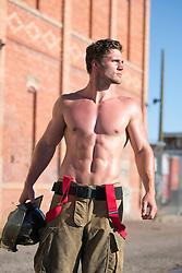 muscular shirtless fireman outdoors