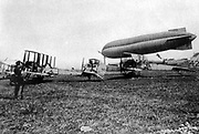Biplanes of the Royal Flying Corps, the British military air arm, parked on the ground, together with an observation balloon. First used for aerial reconnaisance on 13 Septemebr 1914.