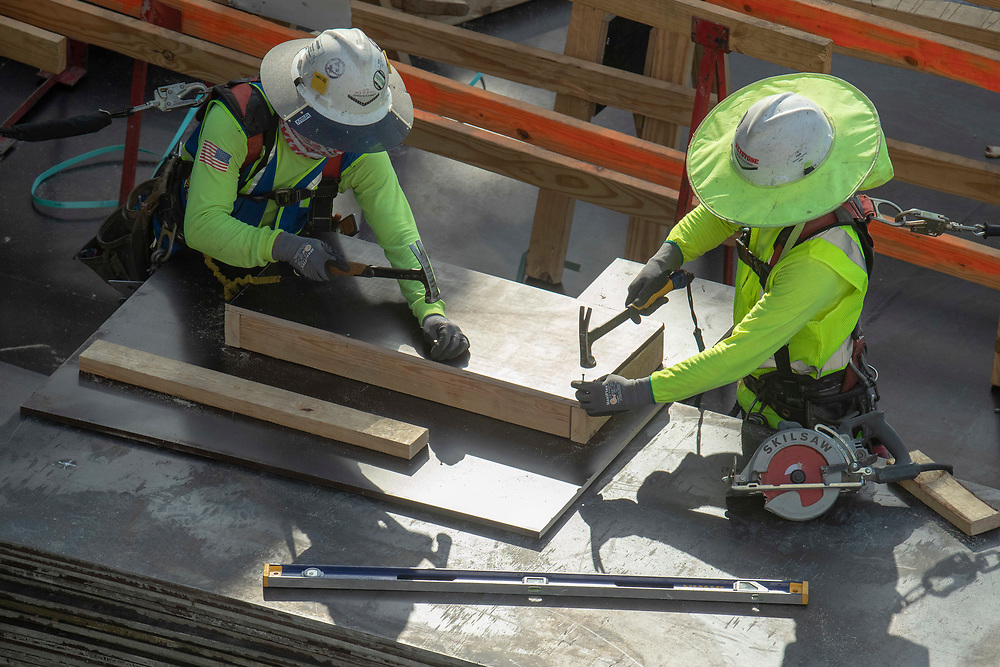 Austin, TX USA July 14, 2020: Construction workers and concrete specialists continue progress on the ground floors of a skyscraper in the Rainey Street district during an eight-hour shift in the 105-degree Texas heat.  Crews are on the second story of a planned 53-story building as they take precautions against the coronavirus pandemic.